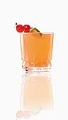 Ein Cocktail mit Cocktailspiesschen vor weißem Hintergrund