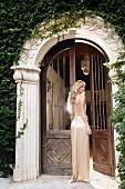 Junge Frau in langem Abendkleid an antikem Eingangsportal