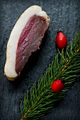 A slice of smoked, marinated duck breast with a sprig of spruce and rose hips on a slate platter