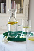 Lemon water in a carafe and in glasses on a tray