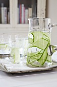 Water with cucumber strips in a carafe and in glasses