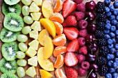 Pieces of fruit laid out in a rainbow