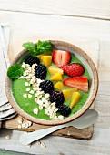 Smoothie-Schale mit Kohl, Apfel und Kiwi, darauf Erdbeeren, Pfirsich, Heidelbeeren und Haferflocken