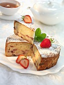 Madeira cake with strawberries and icing sugar, sliced