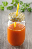Carrot juice in a screw-top jar with a straw