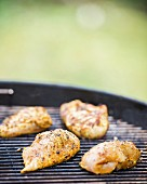Stuffed Oriental-style chicken breasts on a barbecue