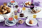 A table laid for breakfast with a purple tablecloth and white plates