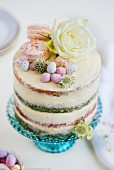 A four-layer ombre cake with white frosting, macaroons, Easter eggs and flowers
