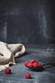 Frische Himbeeren auf Löffel vor dunklem Hintergrund