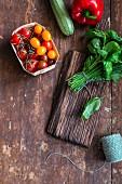 Tomaten, Zucchini, Paprika und Kräutersträusschen auf rustikalem Holztisch
