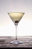 A martini with a caper berry