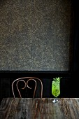 A Mojito on a wooden table against a wall with artistic wallpaper