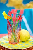Colourful swizzle sticks in plastic beaker on plate