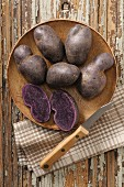 Purple potatoes with a knife on a wooden plate