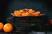 Wedges of Sicilian blood oranges on a plate and in a wooden crate