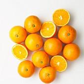 Mehrere Orangen, ganz und halbiert auf weißem Untergrund (Aufsicht)
