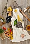 Zutaten und Küchenutensilien für Nudelgerichte auf Kochschürze liegend