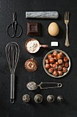 An arrangement of kitchen utensils and baking ingredients on a dark surface