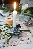 Brennende Kerze an Mistelzweig mit gestapelten Weihnachtsplätzchen