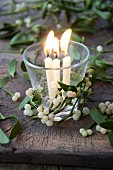 Burning candles in a glass decorated with mistletoe