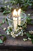 Brennende Kerzen im Glas mit Misteldekoration