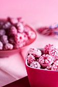 Raspberry sweets in pink bowls on a pink surface