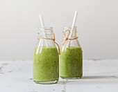 Green smoothies with avocado, kiwi, spinach, ginger and chia seeds in bottles