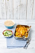 Lemon chicken in a roasting tin with rice and cucumber salad