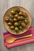 Black tomatoes on wooden plate (seen from above)