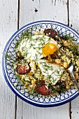 Turkish rice noodles with sausages, fried egg and chickpeas