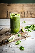 A glass of kiwi and spinach smoothie with fresh spinach leaves and slices of kiwi