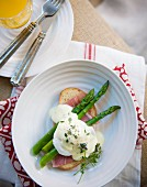 A poached egg on a slice of bread and ham with green asparagus and Hollandaise sauce