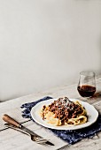 Spaghetti with a red wine and pork ragout and a glass of red wine