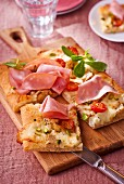 Pizza with mortadella, cheese, pistachios and cherry tomatoes