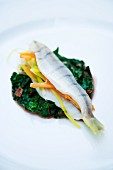A stuffed European perch on red chard