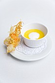 Cream of yellow pepper soup with a crispy prawn on a rice leaf