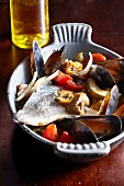 Oven-baked mussels and fish with vegetables