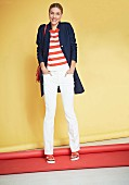 Frau in Ringelpullover, weißer Stoffhose und blauem Kurzmantel