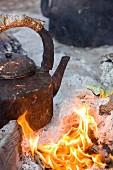 A kettle over an open fire