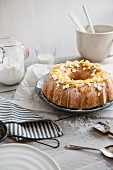 A white chocolate Bundt cake with orange zest on a table with baking utensils