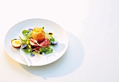A baked egg wrapped in Parmesan cheese and ham on a salad of edible flowers