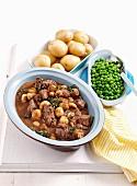 Rindfleisch-Pilz-Ragout aus dem Ofen mit Pellkartoffeln und Erbsen