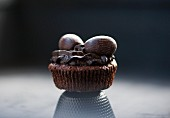 A chocolate cupcake with chocolate frosting and chocolate Easter eggs (close-up)