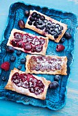 Various berry tarts on a tray