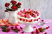 Meringue cake with cream, strawberries and rose petals on a cake stand in front of a vase of red roses