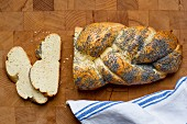A poppyseed plait, sliced, on a wooden surface