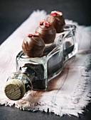 Handgemachte Pralinen in Zartbitterkuvertüre mit Erdbeer-Balsamico-Füllung und Dekor aus getrockneten Erdbeeren auf einer Flasche Aceto balsamico