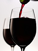 Pouring red wine into glass (close-up)