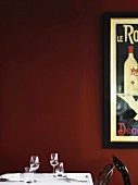 A laid table with wine and water glasses against a dark red wall with a retro advertising poster