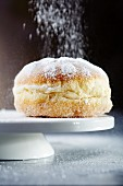 A doughnut being dusted with icing sugar (close-up)